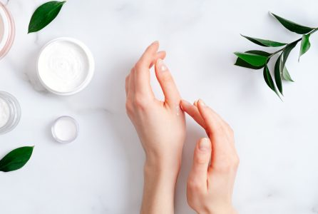 Cosmetic cream on female hands, jars with milk swirl cream and green leaves on white marble table. Flat lay, top view. Woman applying organic moisturizing hand cream. Hand skin care concept